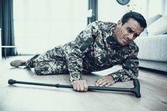 Behindertes Militärlügen auf Boden mit Krücke stockfotos