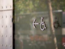 Behindertes Rollstuhllogo des Handikaps, das links außerhalb der Stahlwand auf Gebäude zeigt stockfotografie