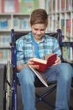 Behindertes Schülerlesebuch in der Bibliothek Lizenzfreies Stockfoto
