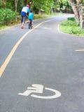 Behindertes Zeichen auf Straße mit undeutlichem Vater und Sohn im Hintergrund Lizenzfreie Stockfotografie