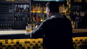 Behing shot of a man quietly sitting at the bar with glass of whiskey, chatting online.