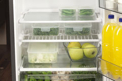 Behållare för frukter och för grönsaker itu i en modern kyl Arkivfoton