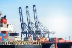 Behälter-Frachtfrachtschiff mit Arbeitskranbrücke im Himmel der Werft in der Dämmerung Stockbild