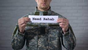 Behoefte rehab woorden die op teken in handen van mannelijke militair, sociale steun worden geschreven stock footage