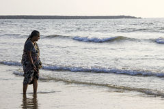 Beholding Sea Waves. Woman curiously observing sea waves at Mangalore, Karnataka, India, Asia Stock Photo