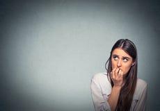Beißende Fingernägel der jungen zögernden nervösen Frau sehnend oder besorgt stockfotografie