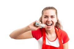 Beißende köstliche Salami des attraktiven weiblichen Supermarktangestellten lizenzfreies stockfoto