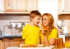 Beißende Pizza des Jungen von der Hand seiner Mama stockbild