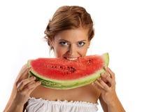Beißende Scheibe der jungen hübschen Frau der Wassermelone Stockfoto