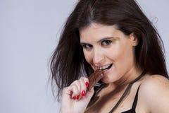Beißende Schokolade der Frau Lizenzfreie Stockfotografie