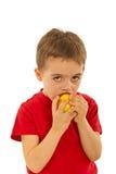 Beißender Apfel des Kindjungen Stockfotos