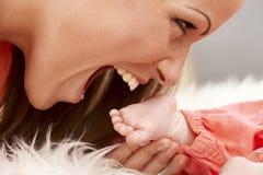 Beißender Babyfuß der Mutter Lizenzfreies Stockfoto