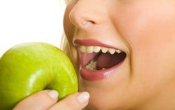 Beißender grüner Apfel der Frau lizenzfreie stockbilder