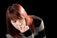 Beißender Nagel des nachdenklichen Redheadmädchens Stockfoto
