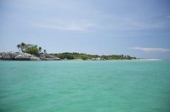 Bei acqua, cielo blu, oceano ed isola verdi Immagine Stock
