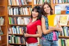Bei allievi femminili in una libreria Fotografia Stock