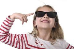 Bei 6 - 8 anni del bambino femminile con capelli biondi che indossano grande sorridere degli occhiali da sole felice ed allegro Fotografia Stock