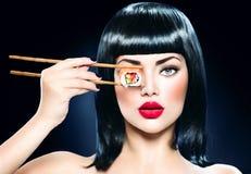 Bei bastoncini della tenuta della donna con il rotolo di sushi Fotografia Stock