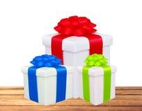Bei contenitori di regalo con gli archi variopinti sulla tavola di legno isolata Fotografia Stock