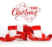 Bei contenitori di regalo con il ramo rosso dei nastri del Buon Natale del testo e dell'albero Iscrizione di calligrafia Immagini Stock