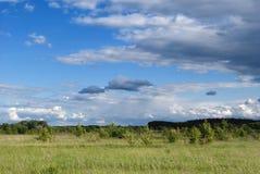 Bei cumuli sopra i prati e campi nella valle Immagine Stock
