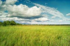 Bei cumuli sopra i prati e campi nella valle Fotografie Stock Libere da Diritti