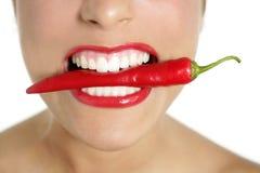 Bei denti della donna che mangiano pepe rosso Immagine Stock