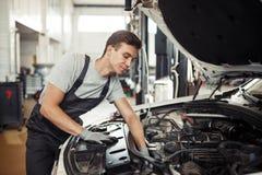 Bei der Arbeit: ein Automechaniker sucht nach Wanzen in einer Maschine stockbilder