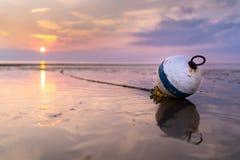 Bei Ebbe Strandsonnenuntergang der Boje stockfotos