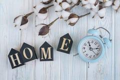 Bei fiori bianchi del cotone, cubi con le lettere e sveglia blu sul fondo di legno del turchese Fotografie Stock