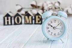 Bei fiori bianchi del cotone, cubi con le lettere e sveglia blu sul fondo di legno del turchese, concetto di mattina Immagini Stock