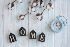 Bei fiori bianchi del cotone, cubi con le lettere e sveglia blu sul fondo di legno del turchese, flatlay Immagine Stock