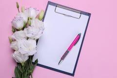 Bei fiori bianchi Mazzo di eustoma con uno spazio in bianco per testo su un fondo rosa luminoso Vista da sopra immagine stock