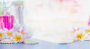 Bei fiori del frangipane con i bolli di erbe della compressa, la lozione rosa e le coperture al fondo della natura di estate Staz Immagine Stock