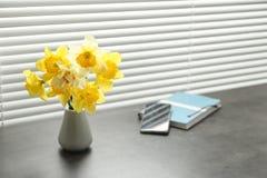 Bei fiori del narciso in vaso vicino alla finestra con i ciechi fotografia stock
