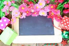Bei fiori e contenitore di regalo sopra il bordo di gesso Fotografia Stock Libera da Diritti