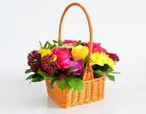 Bei fiori nel canestro del awicker su fondo leggero Immagine Stock