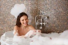 Bei giochi della donna con le bolle nel bagno Cura del corpo fotografie stock libere da diritti