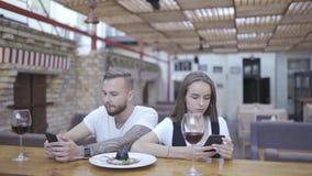 Bei giovane e donna che utilizza gli Smart Phone moderni nel caffè e scrivendo messaggio di testo a macchina sul cellulare stock footage