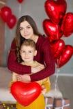 Bei giovane madre castana sveglia della mamma con il suo ragazzo bello dell'adolescente che si tiene insieme e felice Donna dentr Fotografie Stock Libere da Diritti