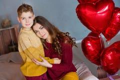 Bei giovane madre castana sveglia della mamma con il suo ragazzo bello dell'adolescente che si tiene insieme e felice Donna dentr Fotografie Stock