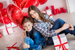 Bei giovane madre castana sveglia della mamma con il suo ragazzo bello dell'adolescente che si tiene insieme e felice Donna dentr Immagine Stock