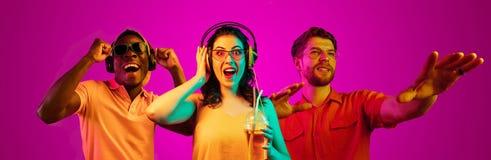 Bei giovani alla luce al neon isolata sul fondo rosa dello studio fotografia stock libera da diritti