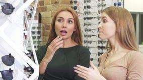 Bei giovani amici femminili felici che scelgono occhiali all'optometrista stock footage
