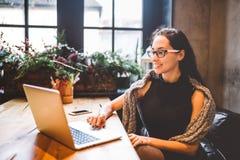 Bei giovani vetri della donna di affari e computer portatile d'uso castana di usi del maglione per stampare testo sulla tastiera  fotografie stock