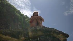 Bei insiemi biondi della donna sulla roccia sulla spiaggia selvaggia di Bali video d archivio