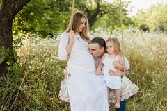 Bei madre e papà incinti con la piccola ragazza bionda in un vestito bianco che si siede su un'oscillazione, ridente, infanzia, r Immagine Stock