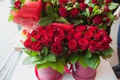 Bei mazzi delle rose rosse in contenitore di regalo, sul davanzale bianco della finestra Immagine Stock