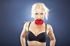 Bei morsi di modello biondi in un lollipop rosso. Immagini Stock