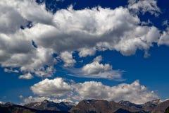 Bei nubi e cielo blu sopra le montagne Immagine Stock
